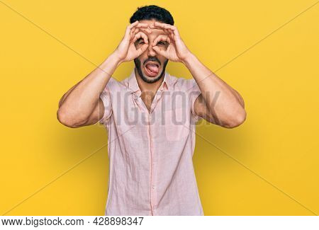 Hispanic man with beard wearing casual shirt doing ok gesture like binoculars sticking tongue out, eyes looking through fingers. crazy expression.