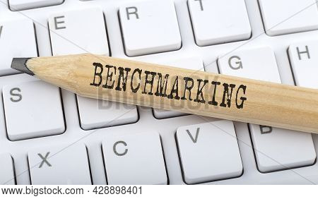 Text Benchmarking On Wooden Pencil On White Keyboard. Business