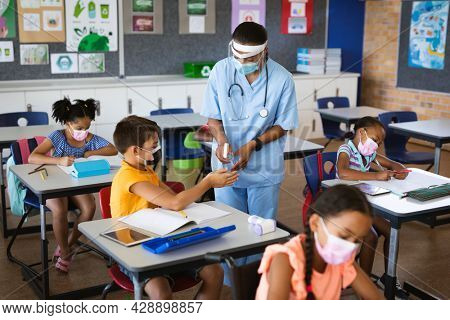 Female health worker spraying hand sanitizer on hands of boy at elementary school. education back to school health safety during covid19 coronavirus pandemic.