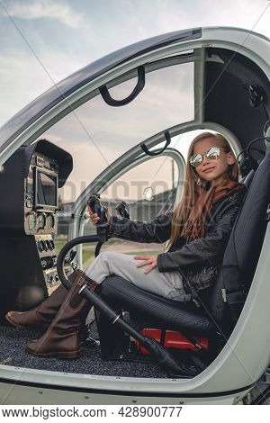 Smiling Tween Girl In Mirrored Sunglasses Sitting In Open Helicopter