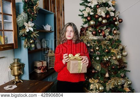 Beautiful Young Woman Celebrating Christmas At Home, Having Fun While Opening Presents