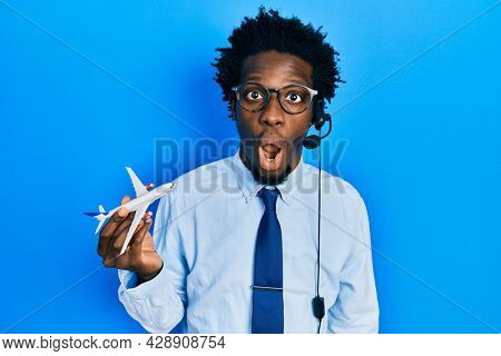Young african american travel agent man holding plane scared and amazed with open mouth for surprise, disbelief face