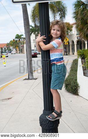 Energetic Boy Child Climb Up Street Lamppost Summer Outdoors, Childhood