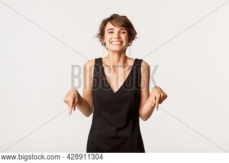 Ecstatic Beautiful Girl Looking Pleased, Smiling And Pointing Fingers Down At Logo, Standing Over Wh
