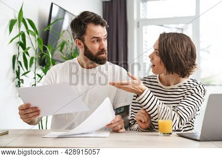 Young angry white couple working together with laptop computer and documents on the table at home holding papers, argue