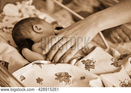 Mother Hands Are Stroking A Newborn Baby With A Maternity Hospital Bracelet On Her Arm. A Newly Born