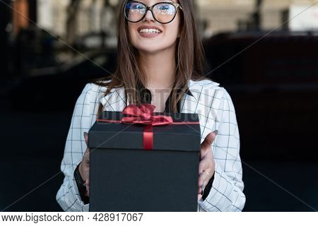 Young Stylish Woman Hands Gift. Happy Young Woman Holds Gift Box And Smiling. Black Gift Box With Re