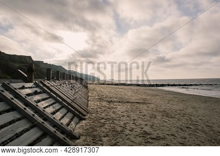 Moody Beach Landscape With Sea Defence East Coast Uk. Sandy Beach With Wooden Sea Defence Structure