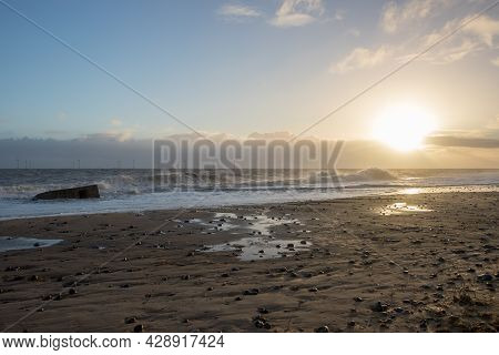 The Coast. East Coast Of England Beach Sunrise Landscape With Distant Offshore Wind Farm Turbines On