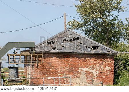 Damaged Roof And Wall. Slate Tiles Falling Off Derelict Agricultural Building. Hole In Roof Of Outbu