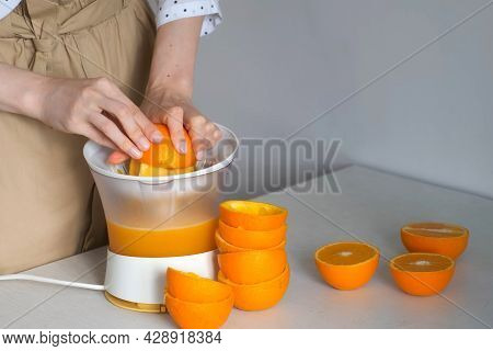 Woman Is Squeezing Oranges Using Electric Juicer In The Kitchen, Closeup View.