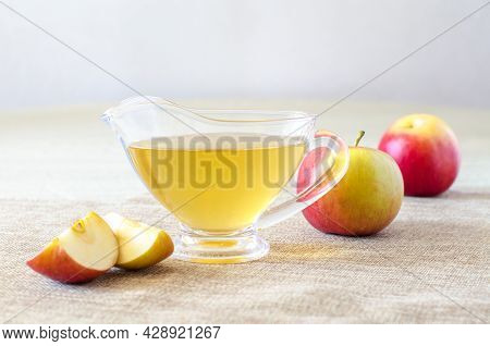 Glass Gravy Boat With Apple Cider Vinegar And Fresh Fruits On A Light Wooden Table. Close-up