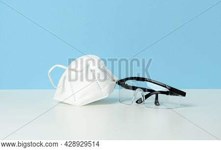Transparent Plastic Protective Medical Glasses And White Disposable Mask On A Blue Background
