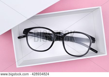 Optical Glasses In A Stylish Black Frame Are In A White Gift Box On A Pink Background.the Concept Of