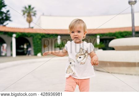 Little Girl Stands On A Terrace Against The Backdrop Of A Long Pavilion Entwined With Greenery