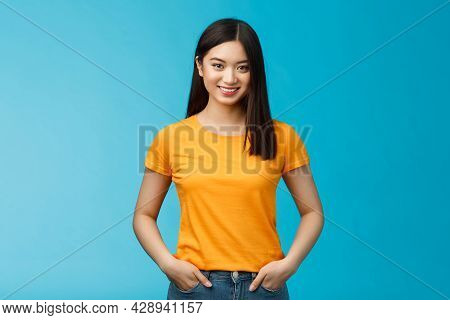 Confident Assertive Smiling Asian Woman Stand Blue Background Look Camera, Hold Hands Jeans Pockets