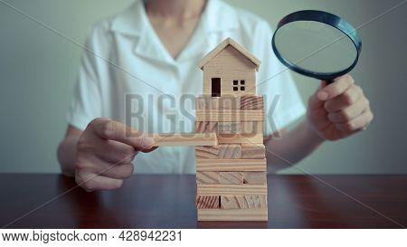 Female Complete Wooden Model Of The House With Last Piece And Using Magnifying Glass Over The Model