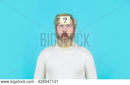 Thinking Man With Question Mark On Blue Background. Man With Question Mark On Forehead Looking Up. P