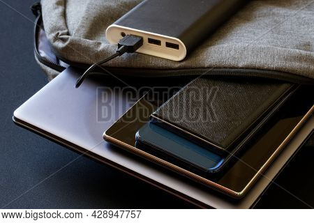 Modern Mobile Gadgets - Tablet, Two Smartphones And Laptop Lie In A Gray City Backpack Next To An Po