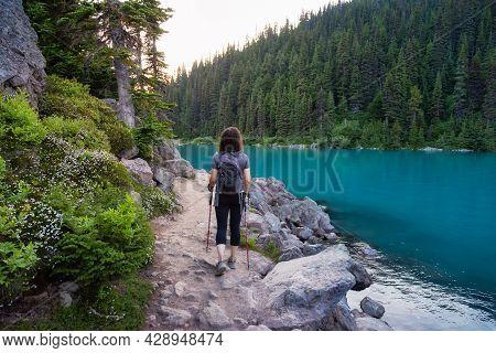 Adventurous White Caucasin Adult Woman Hiking On A Trail In Canadian Nature. Sunset Sky. Garibaldi L