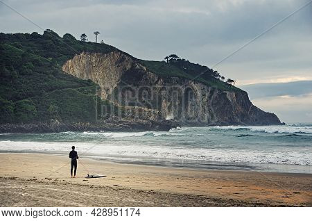 Surfing Concept. Love Surfing. Surfer Standing On The Beach And Looking At Waves In The Ocean. Surfi