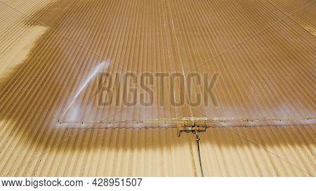 Aerial View Crop Irrigation Machine Using Center Pivot Sprinkler System. An Irrigation Pivot Waterin