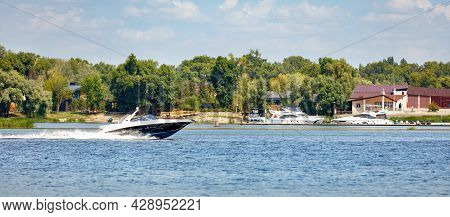 The Motor Boat Moves Quickly Along The Water Surface Of The River.