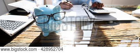 Financial Advisor With Piggybank. Money Saving Calculation