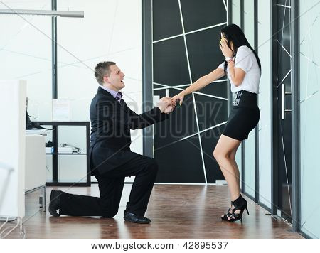 Young man romantically proposing to girlfriend and offering engagement ring at working place