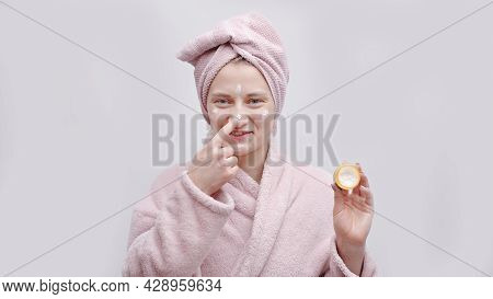Attractive Girl Holding A Small Jar Of Moisturizing Skin Cream. Applying Cream On Her Nose. The Girl