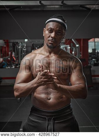 Sports African American Guy With Naked Muscular Torso Standing In Gym. Personal Trainer With Bare Ch
