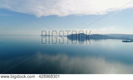 Mirrored Sea Surface With Mountain Coast. Shot. Water Mirrors Blue Sky At Dawn On Background Of Moun