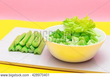 Fresh Chopped Celery Slices In White Bowl With Celery Sticks On White Cutting Board. Vegan And Veget