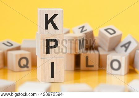 Wooden Cubes With Letters Pfi Arranged In A Vertical Pyramid, Yellow Background, Reflection From The