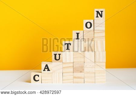 The Word Caution Is Written On A Wooden Cubes, Concept