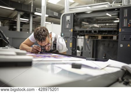 Professional Print Worker Checking Imprint Quality And Color Matching With Magnifying Glass In Print