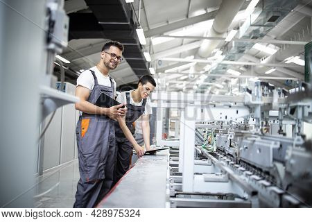 Production Line Workers Controlling Manufacturing Process Of Modern Packaging Industrial Machine In