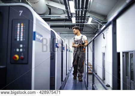 Experienced Man Operator In Working Uniform Controlling Printing Process Of Modern Offset Paper Mach