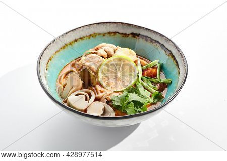 Tom yum or tom yam - hot and sour Thai soup with chicken. Thai traditional soup with chicken and vegetables. Tom yum on white background. Isolated soup plate over white background.