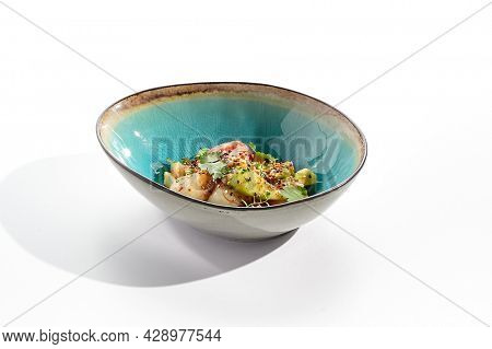 Green salad with sea scallop, avocado and fresh tomato. Summer seafood salad dressing with micro greens. Salad bowl isolated on white background