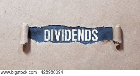 Conceptual Image Of The Word Dividends Written On Label Tag With Coins,dice And Calculator.