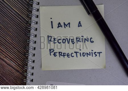 I Am A Recovering Perfectionist Write On Sticky Notes Isolated On Wooden Table.