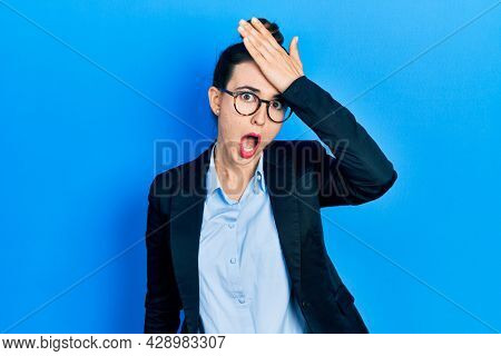 Young hispanic girl wearing business clothes and glasses surprised with hand on head for mistake, remember error. forgot, bad memory concept.