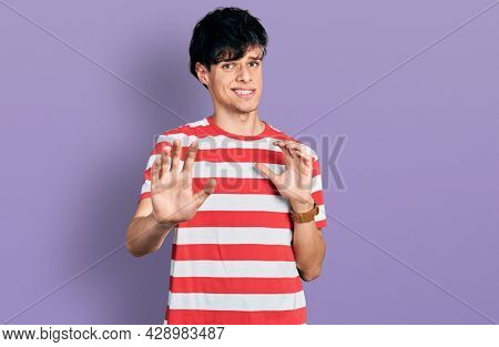Handsome hipster young man wearing casual striped t shirt disgusted expression, displeased and fearful doing disgust face because aversion reaction. with hands raised