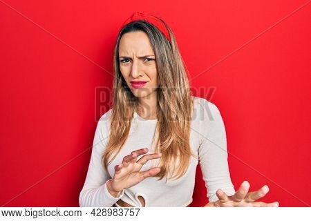 Beautiful hispanic woman wearing red diadem disgusted expression, displeased and fearful doing disgust face because aversion reaction. with hands raised