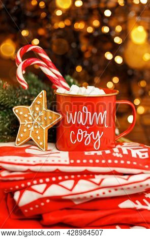 Hot Coffee Or Cocoa With Candy Canes And Marshmallows. Christmas Cappuccino In Red Mug On Red Blanke