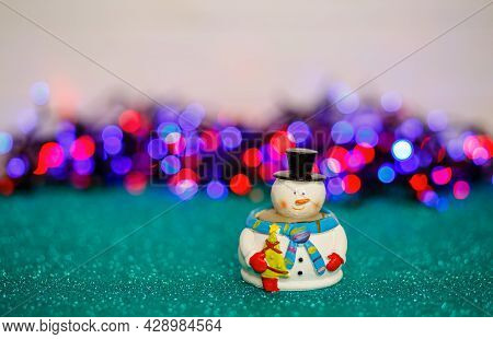 Christmas Snowman On The Table Against A Bokeh Lights Back. Snowman On Abstract Background. Snowman