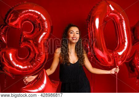 Portrait Of Happy 30 Year Old Woman On Red Background With Red Balloons. A Beautiful Girl Of Caucasi