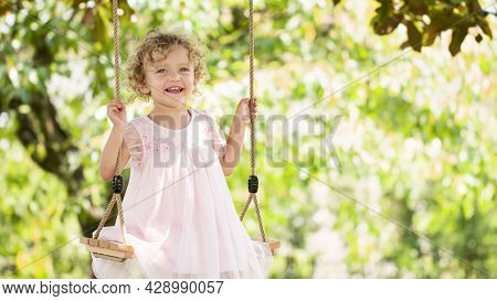 Joyful Smiling Little Girl Swinging On The Swing, Child With Blue Eyes And Curly Blond Hair Plays In