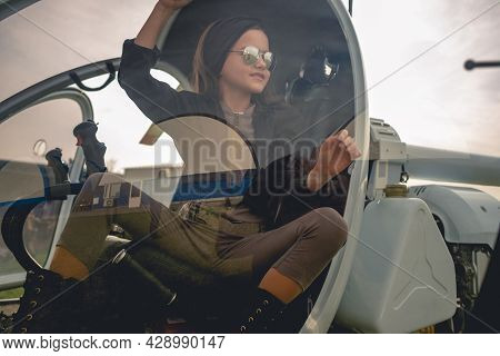 View Through Glass Of Helicopter Cockpit Of Smiling Preteen Girl On Pilots Seat
